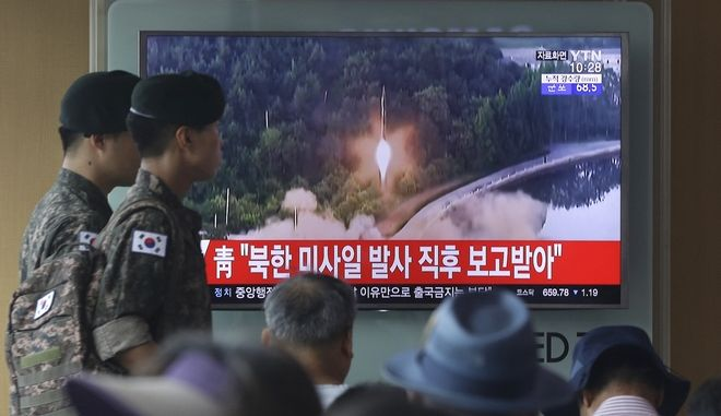 """Army soldiers walk by a TV news program showing a file image of a missile being test-launched by North Korea at the Seoul Railway Station in Seoul, South Korea, Tuesday, July 4, 2017. North Korea on Tuesday launched yet another ballistic missile in the direction of Japan, South Korean officials said, part of a string of recent test-firings as the North works to build a nuclear-tipped missile that could reach the United States. The signs read """"The presidential Blue House was briefed immediately after the North Korean missile was fired."""" (AP Photo/Ahn Young-joon)"""