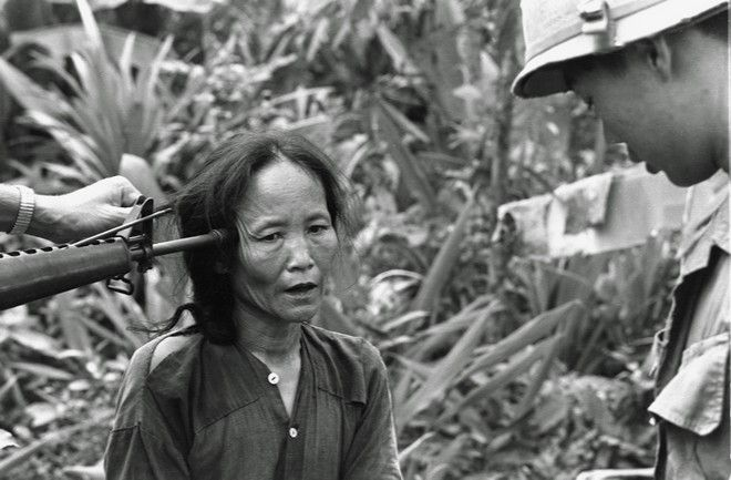 A female Viet Cong suspect is questioned at gunpoint by a South Vietnamese national police officer at Tam Ky, about 350 miles north of Saigon, November 1967.  The M-16 rifle was held by a U.S. soldier during an operation of the 101st Airborne Brigade, searching villages of the coastal plains for suspected Viet Cong enclaves.  (AP Photo)