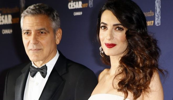 Actor George Clooney and Amal Clooney pose at the 42nd Cesar Film Awards ceremony at Salle Pleyel in Paris, Friday, Feb. 24, 2017. This annual ceremony is presented by the French Academy of Cinema Arts and Techniques. (AP Photo/Francois Mori)