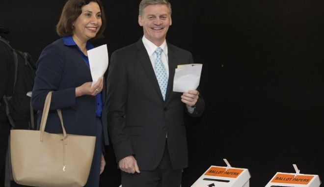 New Zealand Prime Minister Bill English and his wife Dr Mary English pose for a photo as they prepare to cast their votes at a early voting booth in Wellington, New Zealand, Thursday, Sept. 21, 2017. English is fighting to keep his job when the nation votes in the general election on Saturday Sept. 23. (Mark Mitchell/New Zealand Herald via AP)
