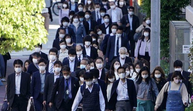 Κόσμος με μάσκες στο Τόκιο (AP Photo/Eugene Hoshiko)