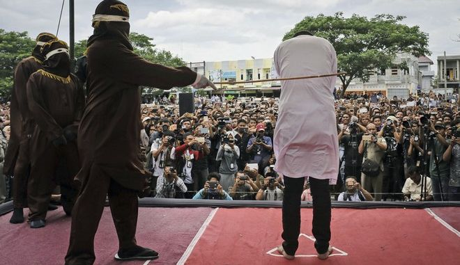 In this Tuesday, May 23, 2017, photo, a Shariah law official whips one of two men convicted of gay sex during a public caning outside a mosque in Banda Aceh, Aceh province Indonesia. More than a thousand people packed a mosque courtyard Tuesday to witness the caning. (AP Photo/Heri Juanda, File)