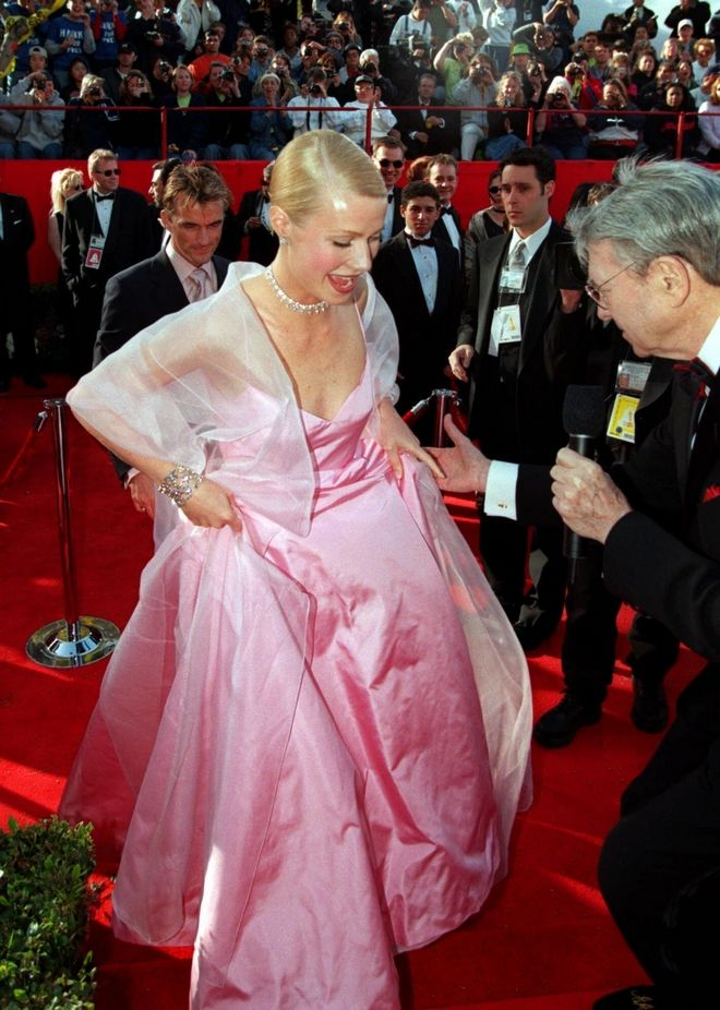 British actress Gwyneth Paltrow lifts the hem of her skirt to speak to a television reporter as she arrives for the 71st annual Academy Awards ceremony Sunday March 21, 1999 in Los Angeles. Paltrow was nominated in the best actress category for her work in