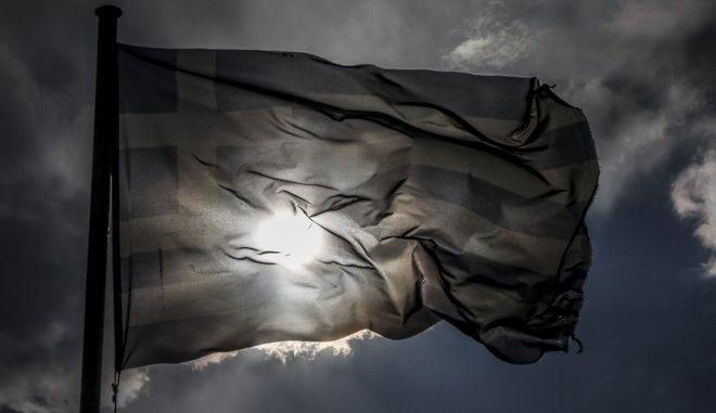 Ελληνική σημαία κυματίζει κάτω από τον συννεφιασμένο ουρανό