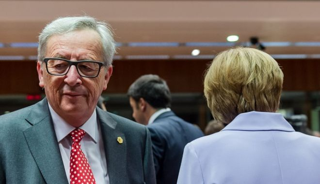 European Commission President Jean-Claude Juncker, left, walks by German Chancellor Angela Merkel during a round table meeting at an EU summit in Brussels on Thursday, June 25, 2015. Greece and its creditors launched a new round of talks in Brussels early Thursday in a fresh bid to unlock billions of euros in loans and save the country from bankruptcy. (AP Photo/Geert Vanden Wijngaert)