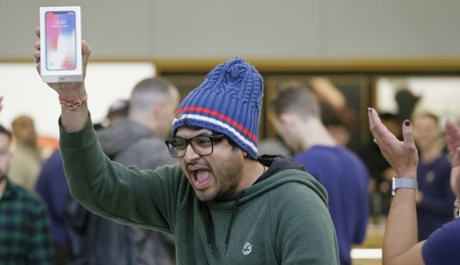 Shalin Mobi, of India, reacts after being the first person to purchase the new iPhone X at the Apple Union Square store Friday, Nov. 3, 2017, in San Francisco. AP Photo/Eric Risberg)