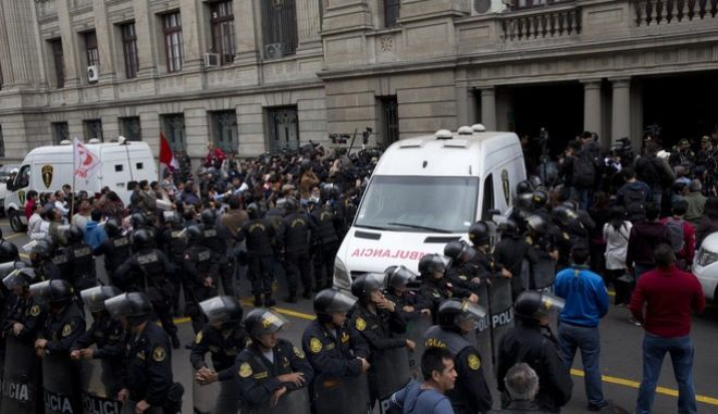 Police stand guard outside the Palace of Justice, where Peru's former President Ollanta Humala and his wife are being held, before their transfer to a jail, in Lima, Peru, Friday, July 14, 2017. A judge ordered the arrest of Humala and his wife on Thursday night as they face money laundering and conspiracy accusations tied to a construction scandal involving Brazilian company Odebrecht. (AP Photo/Rodrigo Abd)