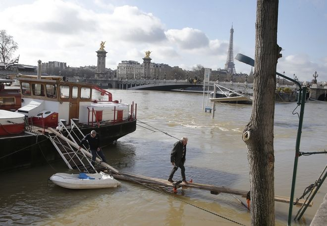 A man crosses a self maid ramp over the Seine river in Paris, France, Friday, Jan. 26, 2018 The Paris region has been deeply affected by the floods that hit the country over the past week, but in Paris, it was business as usual. (AP Photo/Michel Euler)