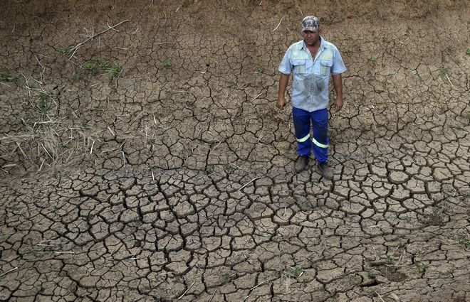 Riaan du Plessis, a farmer, stands on the cracked earth that three weeks ago was the bottom of a reservoir on his farm in Groot Marico, South Africa, Thursday, Nov. 12, 2015. Six of South Africa's nine provinces, including the North West province where the Du Plessis have a farm, have been hit by drought, with three provinces declared disaster areas. (AP Photo/Themba Hadebe)