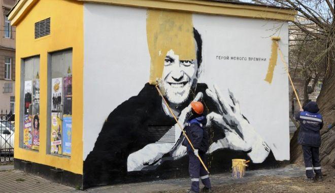 Εργαζόμενοι του δήμου βάφουν με κίτρινο χρώμα το γκράφιτι που απεικονίζει τον Αλεξέι Ναβάλνι