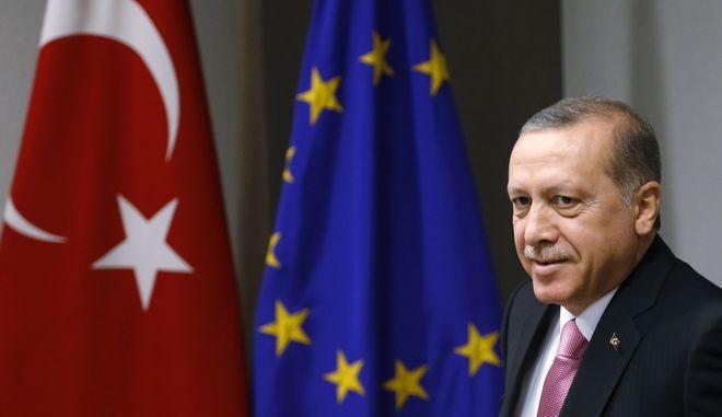 Ο Ρετζέπ Ταγίπ Ερντογάν με φόντο τις σημαίες της Τουρκίας και της ΕΕ