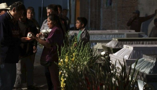 CORRECTS AGE OF BABY TO TWO MONTHS, NOT TWO YEARS - Mourners hold a wake for 11 family members who were killed inside the Santiago Apostol church during the 7.1 earthquake in the town of Atzala in Puebla state, Mexico, Wednesday, Sept. 20, 2017. According to family related to 11 relatives who died inside the church during Tuesday's quake, the roof collapsed during a Mass held to baptize a two-month-old girl, and the only people who survived were the baby's father, the priest and the priest's assistant. (AP Photo/Pablo Spencer)