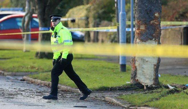 Police attend the scene where a stolen car crashed into a tree Saturday and killed several pedestrians in Leeds, England, Sunday Nov. 26, 2017.   Police say five males including three children were killed Saturday night in Leeds when a stolen car collided with a tree, and reported that two 15-year olds are in police custody but gave no further details. (Danny Lawson/PA via AP)