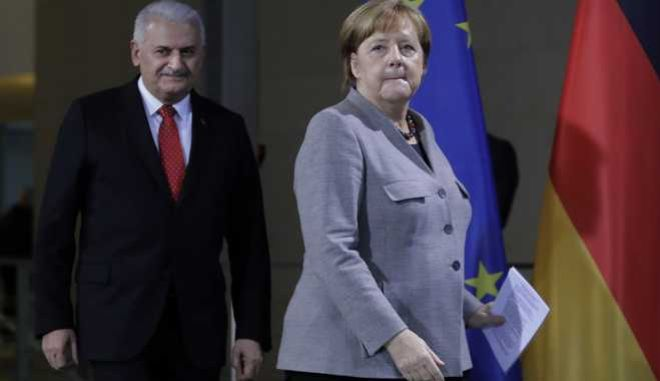 German Chancellor Angela Merkel, right, and Turkish Prime Minister Binali Yildirim arrive to a press conference after a meeting in the chancellery in Berlin, Germany, Thursday, Feb. 15, 2018. (AP Photo/Markus Schreiber)