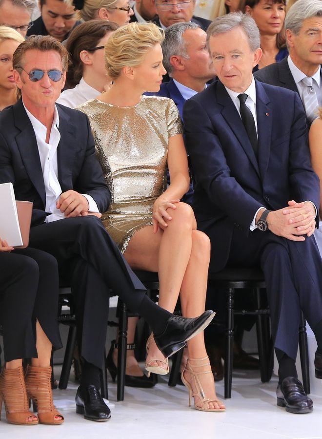 Ο Μπερνάρ Αρνό με τους αστέρες του Χόλιγουντ Σον Πεν και Σαρλίζ Θερόν σε επίδειξη του Ντιόρ στο Παρίσι τον Ιούλιο του 2014