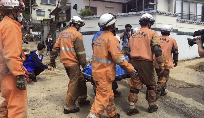 Διασώστες στην Ιαπωνία, μεταφέρουν άτομο που εντόπισαν νεκρό