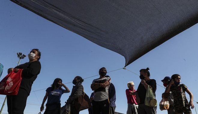 Πολίτες της Χιλής με μάσκες (AP Photo/Esteban Felix)