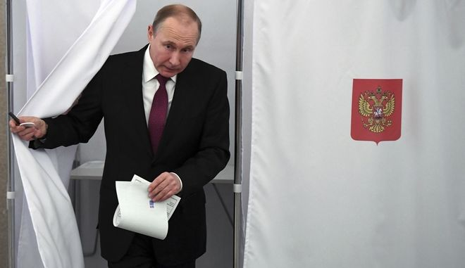 Russian President and Presidential candidate Vladimir Putin exits a polling booth as he prepares to cast his ballot during Russia's presidential election in Moscow, Russia, Sunday, March 18, 2018. Putin's victory in Russia's presidential election Sunday isn't in doubt. The only real question is whether voters will turn out in big enough numbers to hand him a convincing mandate for his fourth term  and many Russian workers are facing intense pressure to do so. (Yuri Kadobnov/Pool Photo via AP)