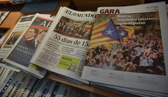 Spanish newspapers announce the breaking news in their front page the independence of the Catalonia region reading in one of them, right, ''Catalan Republic is Born'', in Pamplona, northern Spain, Saturday, Oct. 28, 2017, a day after Catalonia's regional parliament announced the new Republic of Catalonia.(AP Photo/Alvaro Barrientos)