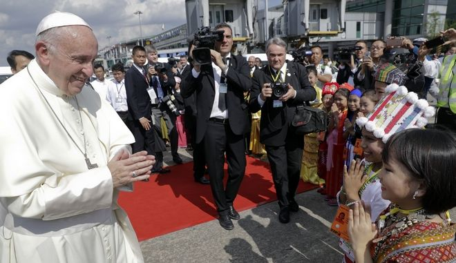 Pope Francis is greeted by children in traditional clothes upon his arrival at Yangon's airport, Myanmar, Monday, Nov. 27, 2017. The pontiff is in Myanmar for the first stage of a week-long visit that will also take him to neighboring Bangladesh. (AP Photo/Andrew Medichini)