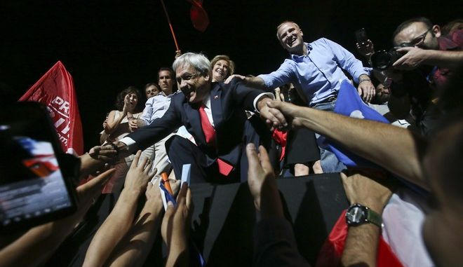 Chile's former President Sebastian Pinera greets supporters as they celebrate his winning the presidential election runoff in Santiago, Chile, Sunday, Dec. 17, 2017. (AP Photo/Esteban Felix)