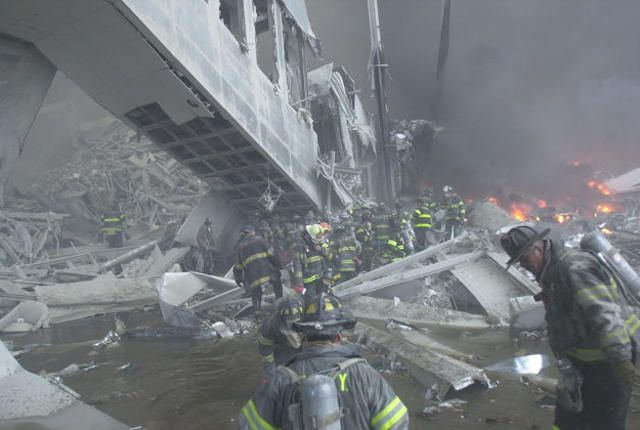 Firefighters look for survivors in the rubble of the World Trade Center after it was struck by a commercial airliner in a terrorist attack. A hijacked American Airlines Boeing 767, originating from Boston's Logan Airport, struck 1 World Trade Center (north tower) at 8:45 a.m. At 9:03 a.m., a United Airlines 767, also hijacked in Boston, crashed into 2 World Trade Center (south tower). Both towers later collapsed.