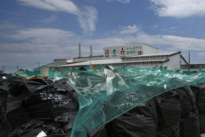 In this July 20, 2016, photo, bags of radioactive waste sit outside the incineration facility in Tomioka, Fukushima Prefecture, northeastern Japan. Japan's nuclear policy-setting Atomic Energy Commission has issued a report calling for nuclear energy to remain a key component of the country's energy mix despite broad public support for a less nuclear-reliant society. (AP Photo/Shizuo Kambayashi)