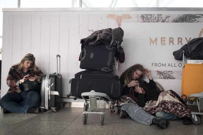 Passengers sit in Stansted Airport terminal, Thursday Dec. 28, 2017, where some passengers were stranded overnight after flights were cancelled due to weather conditions. Met Office forecasters said Britain may face the coldest night of the year so far on Thursday and said snow predicted for parts of northern England may spread to a wider area. (Stefan Rousseau/PA via AP)