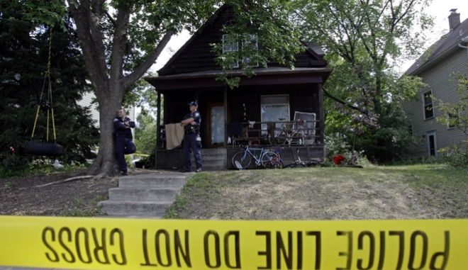 Minneapolis police stand watch over a house that is being searched during the Republican National Convention in Minneapolis, Saturday, Aug. 30, 2008.   Police raided three Minneapolis homes on Saturday, just a few hours after Ramsey County sheriff's deputies raided an organizing site of a group seeking to disrupt the convention.(AP Photo/Matt Rourke)