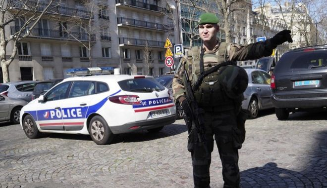 A soldier directs the traffic after letter bomb exploded at the French office of the International Monetary Fund, lightly injuring one person, Thursday March 16, 2017. A police official said no other damage was been reported in the incident. (AP Photo/Thibault Camus)