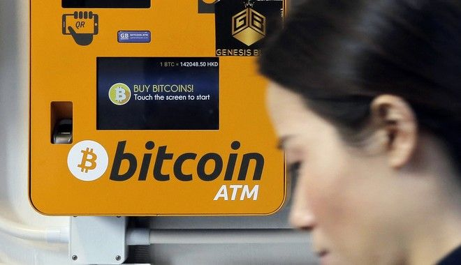 FILE - In this Dec. 21, 2017 file photo, a woman walks past the Bitcoin ATM in Hong Kong. The growth of bitcoin is fueling speculation about the environmental impact of the energy needed to power the cryptocurrency, stemming from the process of