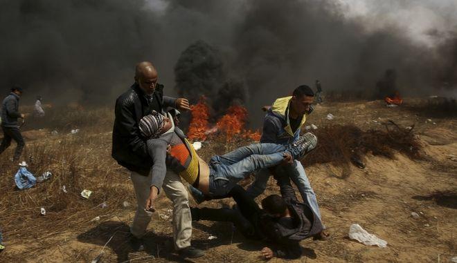 Παλαιστίνιοι διαδηλωτές προσπαθούν να απομακρύνουν ένα τραυματία απ' τη Λωρίδα της Γάζας
