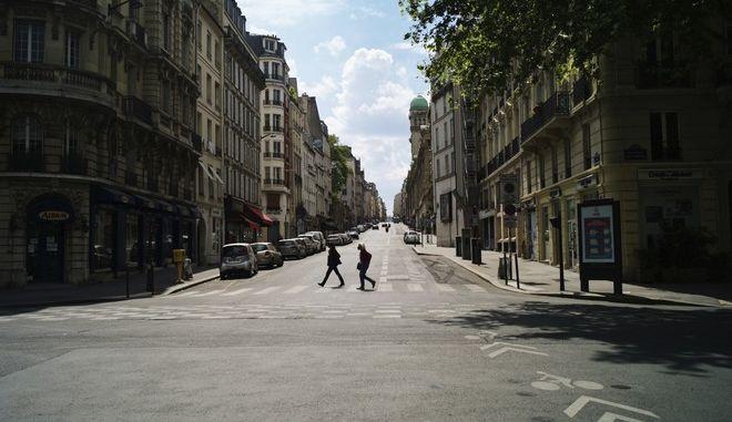 Άνθρωποι περπατάνε σε άδειο δρόμο του Παρισιού