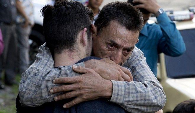 Πατέρας αγκαλιάζει τον γιο του, που σώθηκε μετά από πολύνεκρο ατύχημα με λεωφορείο στο Ελ Σαλβαδόρ