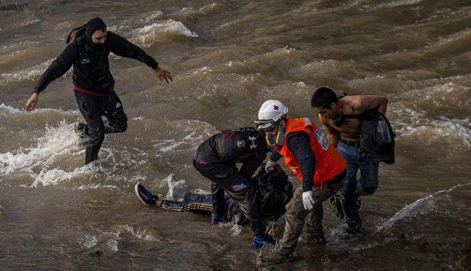 Διασώστες και διαδηλωτές ανασύρουν τον νεαρό απότο ποτάμι.