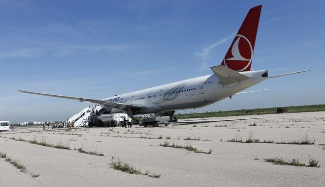 """A Turkish Airlines aircraft sits on a runway away from the airport building of Casablanca, Morocco, Monday, March 30, 2015. Turkish Airlines said it diverted an Istanbul-to-Sao Paulo flight to Casablanca, Morocco, after finding a note with the word """"bomb"""" in the toilet. The airline says it is standard procedure to make an emergency landing under such circumstances. The airline said the Boeing 777 with the flight number TK15 is carrying 256 people. (AP Photo/Abdeljalil Bounhar)"""