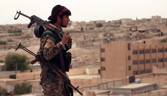 FILE -- In this Sunday, April 30, 2017, file photo, provided by the Syria Democratic Forces (SDF), shows a fighter from the SDF carrying weapons as he looks toward the northern town of Tabqa, Syria. As the U.S.-led coalition ratchets up military operations in Syria ahead of a long awaited assault on the Islamic State groups de facto capital Raqqa, the legacy of an Iraqi train and equip program _ though it has had some success _ is also marked by allegations of abuse and $1 billion dollars in unaccounted for weapons, highlighting the perils of empowering local forces in the fight against IS. (Syrian Democratic Forces, via AP, File)