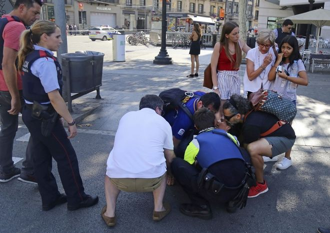 A person is treated in Barcelona, Spain, Thursday, Aug. 17, 2017 after a white van jumped the sidewalk in the historic Las Ramblas district, crashing into a summer crowd of residents and tourists and injuring several people, police said. (AP Photo/Oriol Duran)