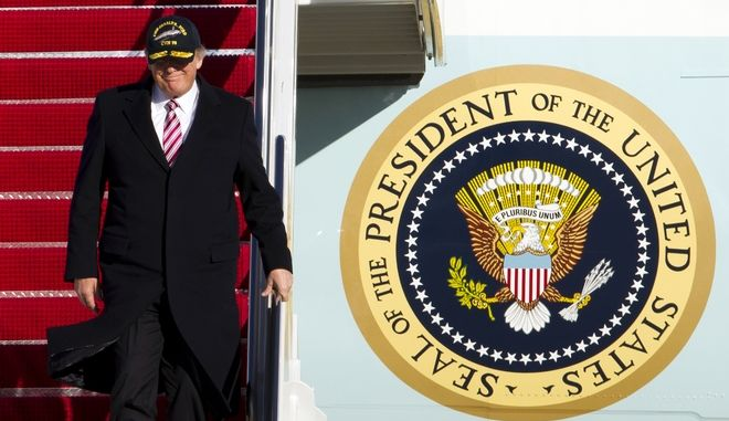 President Donald Trump, wearing at hat from the Gerald R. Ford CVN 78 aircraft carrier, walks down the stairs of Air Force One upon his arrival at Andrews Air Force Base, Md., Thursday, March 2, 2017. Trump returned from Virginia after meeting with sailors and shipbuilders on the aircraft carrier, that is expected to be commissioned this year after cost overruns and delays. ( AP Photo/Jose Luis Magana)