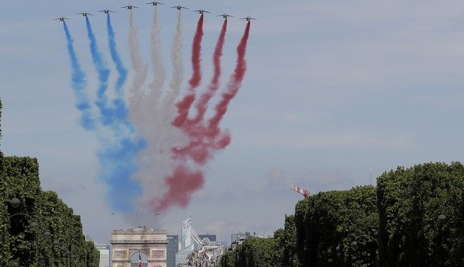 French Alphajets of the Patrouille de France fly over the Champs Elysees avenue, with the Arc de Triomphe in background, during the Bastille Day parade in Paris, Friday, July 14, 2017. Paris has tightened security before its annual Bastille Day parade, which this year is being opened by American troops with President Donald Trump as the guest of honor to commemorate the 100th anniversary of the United States' entry into World War I. (AP/Photo/Markus Schreiber)
