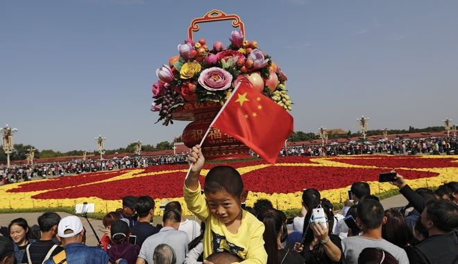 A Chinese boy waves a national flag on his father's shoulder as visitors gather near a giant basket decorated with replicas of flowers and fruits on display at Tiananmen Square on China's National Day in Beijing, Sunday, Oct. 1, 2017. Hundreds of thousands foreign and domestic tourists flock to the square to celebrate the 68th National Day and the Mid-Autumn Festival over the week-long holidays. (AP Photo/Andy Wong)