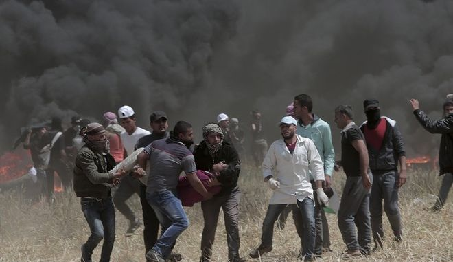 Palestinian protesters evacuate a wounded youth during clashes with Israeli troops along Gaza's border with Israel