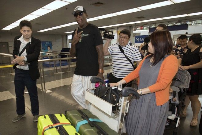 Former NBA basketball player Dennis Rodman, second from left, gestures to photographers as he arrives at Beijing Capital International Airport in Beijing, Tuesday, June 13, 2017. North Korea is expecting another visit by Rodman on Tuesday in what would be his first to the country since President Donald Trump took office. (AP Photo/Mark Schiefelbein)