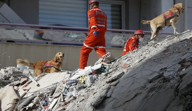 Members of rescue services with sniffer dogs search in the debris of a collapsed building for survivors in Izmir, Turkey, Sunday, Nov. 1, 2020. Rescue teams continue ploughing through concrete blocs and debris of collapsed buildings in Turkey's third largest city in search of survivors of a powerful earthquake that struck Turkey's Aegean coast and north of the Greek island of Samos, Friday Oct. 30, killing dozens Hundreds of others were injured.(AP Photo/Darko Bandic)