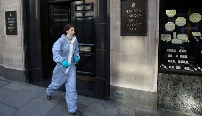 LONDON, ENGLAND - APRIL 07:  A woman believed to be a police forensics officer emerges from a Hatton Garden safe deposit centre on April 7, 2015 in London, England. Police are investigating a break in that occured over the Easter weekend. Local reports say that up to 300 deposit boxes may have been targeted.  (Photo by Peter Macdiarmid/Getty Images)