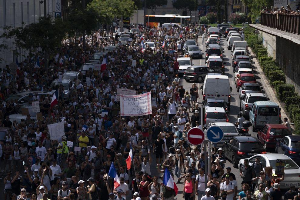 Διαδηλωτές σε πορεία της Γαλλίας, στις 14/8 του 2021, διαμαρτύρονται για την απαγόρευση εισόδου σε χώρους διασκέδασης, τρένα κλπ σε ανεμβολίαστους.