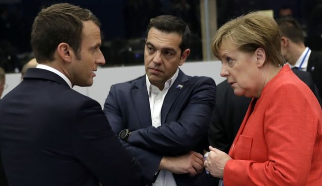 French President Emmanuel Macron, left, speaks with Greek Prime Minister Alexis Tsipras, center, and German Chancellor Angela Merkel during a working dinner meeting at the NATO headquarters during a NATO summit of heads of state and government in Brussels on Thursday, May 25, 2017. US President Donald Trump inaugurated the new headquarters during a ceremony on Thursday with other heads of state and government. (AP Photo/Matt Dunham, Pool)