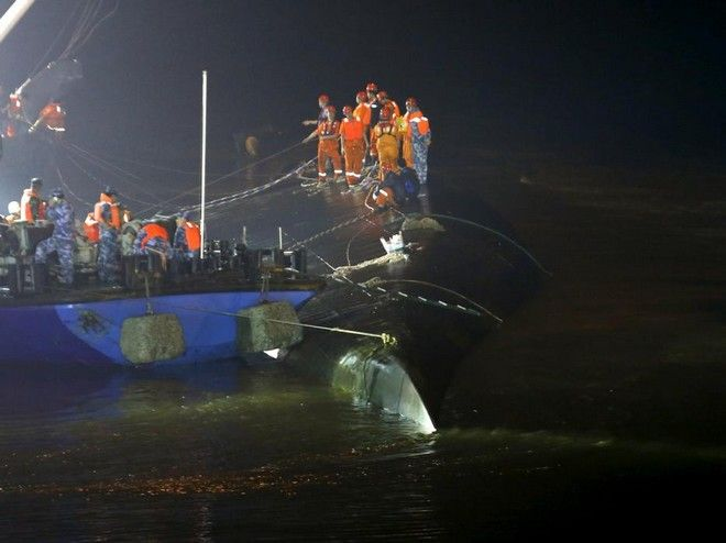Rescue workers are seen atop a sunken ship in the Jianli section of Yangtze River, Hubei province, China, June 2, 2015. Rescuers fought bad weather on Tuesday as they searched for more than 400 people, many of them elderly Chinese tourists, missing after a cruise boat was buffeted by a freak tornado and capsized on the Yangtze River.  REUTERS/Kim Kyung-Hoon