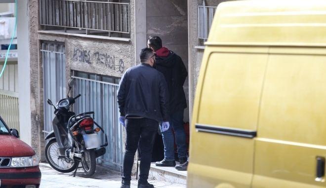 Αστυνομικοί ερευνούν τη είσοδο της πολυκατοικίας στου Γκύζη, όπου βρέθηκε νεκρός 66χρονος άνδρας.