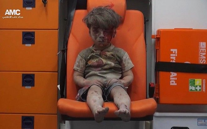 2016 AP YEAR END PHOTOS - In this frame grab taken from video provided by the Syrian anti-government activist group Aleppo Media Center (AMC), 5-year-old Omran Daqneesh sits in an ambulance after being pulled out of a building hit by an airstrike in Aleppo, Syria, on Aug. 17, 2016. The White Helmets were among the crowd of first responders who pulled Daqneesh and his family from the rubble of their apartment building. (Aleppo Media Center via AP, File)